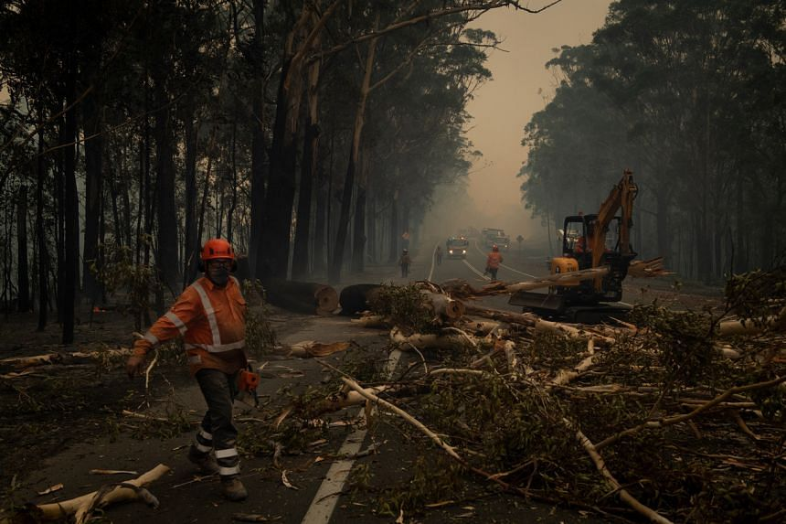 Crews clear debris from a roadway near Jerrawangala, Australia on Jan. 2, 2020.