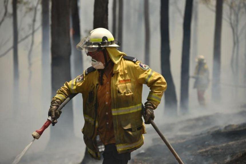 Firefighters tackle a bushfire near Batemans Bay in New South Wales on Jan 3, 2020.