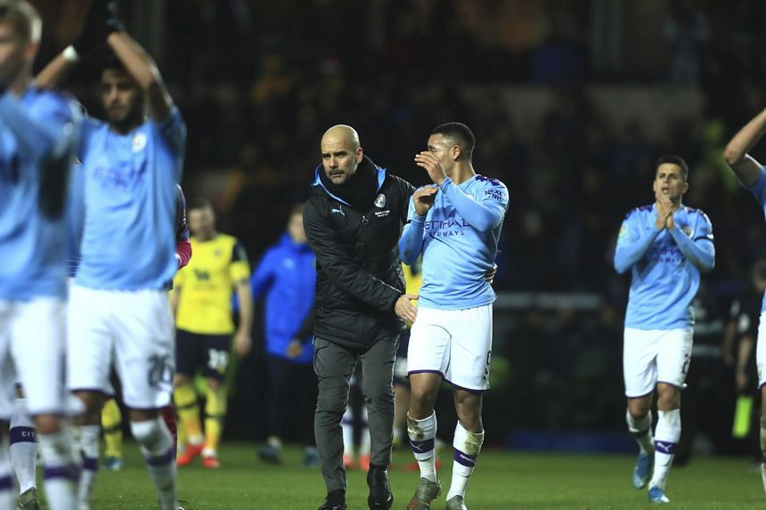 Manchester City's head coach Pep Guardiola (centre) celebrates with Gabriel Jesus at the end of an FA Cup quarter final match against Oxford United at Kassam stadium in Oxford on Dec 18, 2019.