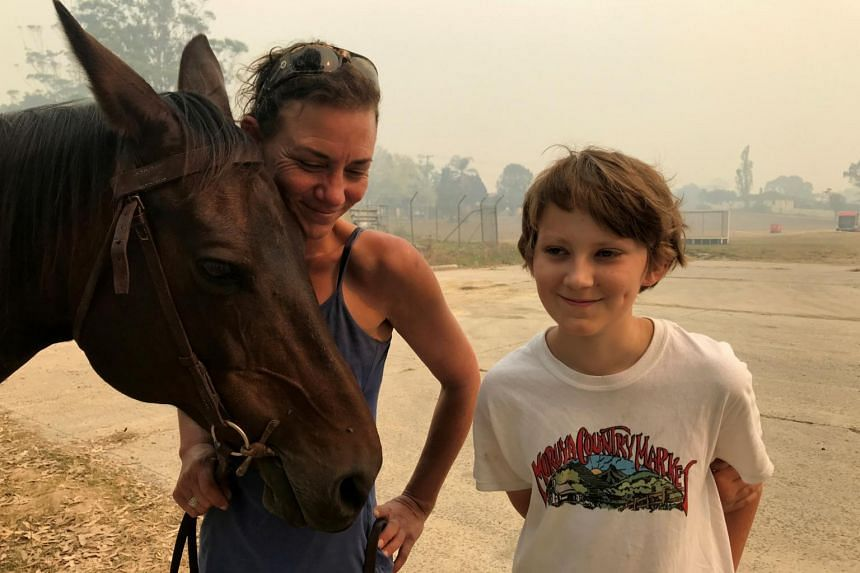 Bec Winter stands next to her son, Riley, while hugging her horse Charmer, who she rode to safety through bush fires on New Year's Eve, in Moruya, Australia, on Jan 4, 2020.