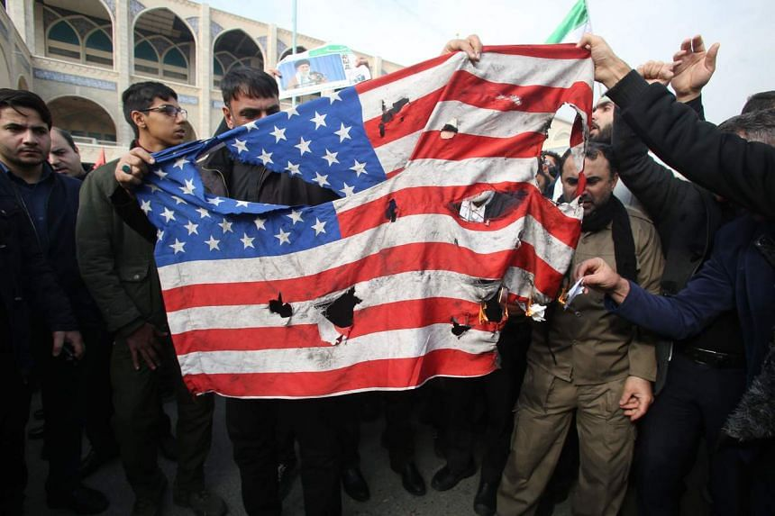 Iranians burn a US flag during a demonstration in Teheran on Jan 3, 2020.