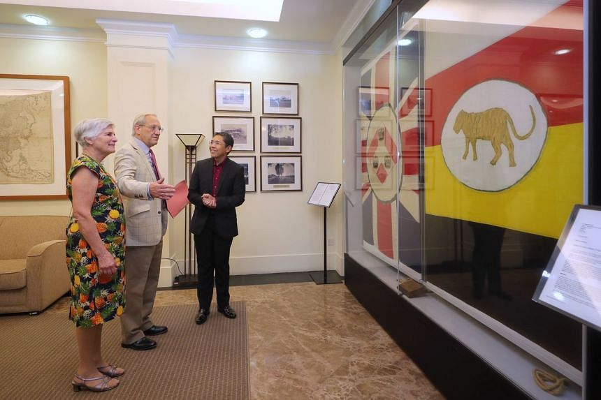 Senior Minister of State for Defence and Foreign Affairs Maliki Osman with Mr Nicholas Sherman and his wife Rosemary at the Ministry of Foreign Affairs yesterday, viewing the Union flag (left) and the flag of the Federated Malay States that were previousl