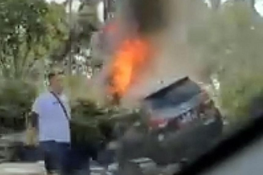 A car on fire after it crashed into the road divider on the East Coast Parkway yesterday. Video footage showed the car lodged among shrubs along the divider, with smoke billowing from it. PHOTO: PATRICK TAN/FACEBOOK The scene of the car fire incident