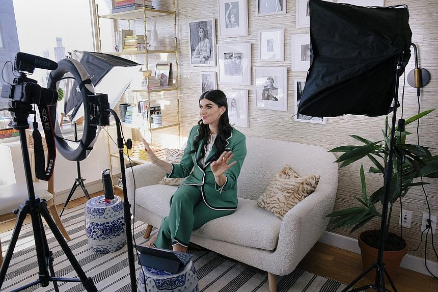 Ms Haley Sacks, aka @MrsDowJones, working on a YouTube video at her apartment in Manhattan. The 28-year-old has built a personal brand by creating memes and videos about investment banking and wealth generation.