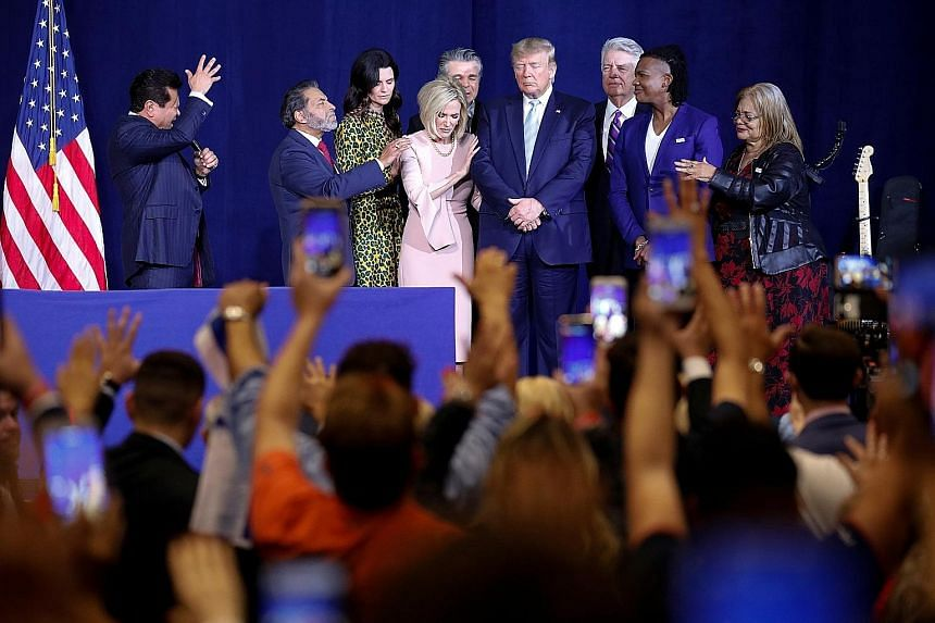 Pastor Guillermo Maldonado of El Rey Jesus church in Miami praying for US President Donald Trump before the latter's speech to evangelical supporters in Miami on Friday. Those on stage included Ms Cissie Graham Lynch (in yellow and black dress).