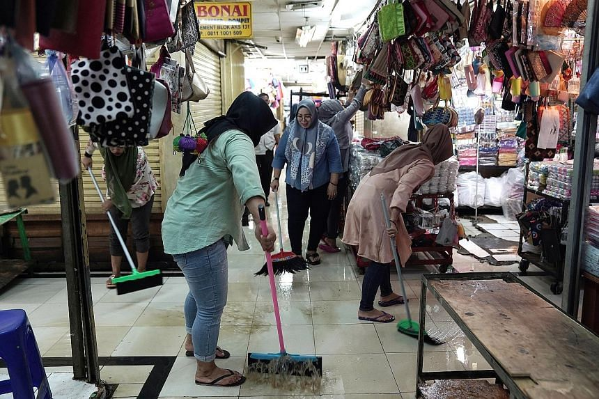 Workers sweeping away flood water outside stores at a shopping centre in the Jatinegara district of Jakarta yesterday.