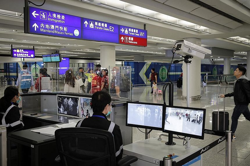 Health surveillance officers using temperature scanners to monitor passengers arriving at Hong Kong International Airport yesterday, amid fears about a mysterious infectious disease that has appeared in China.