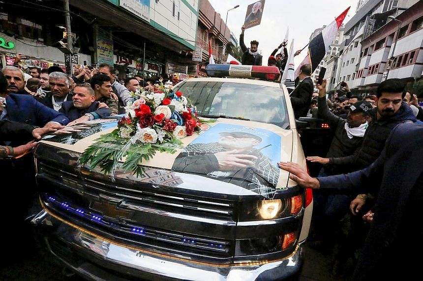Above: Mourners surrounding a car carrying the coffin of Iran's military chief Qassem Soleimani. Left: Supporters of Iraq's Hizbollah brigades weep at the funeral. PHOTOS: AGENCE FRANCE-PRESSE