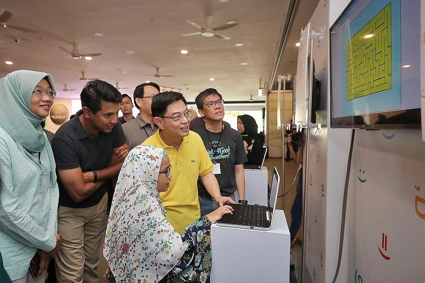 Deputy Prime Minister Heng Swee Keat and Google vice-president Caesar Sengupta looking at Sephia Rindiani Andi's colourful maze project at yesterday's graduation ceremony for students who completed the programme last year.