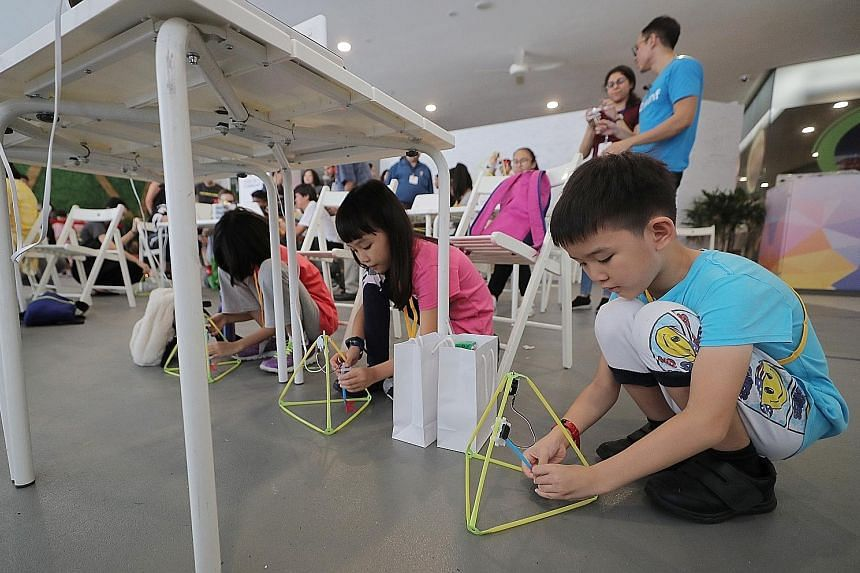 (From right) Siblings Ma Junlong, eight, and Ma Xiangyu, 10, building walking robots at a taster class for Code in the Community's new applications programme at Our Tampines Hub yesterday. The programme will introduce more complex ideas and encourage