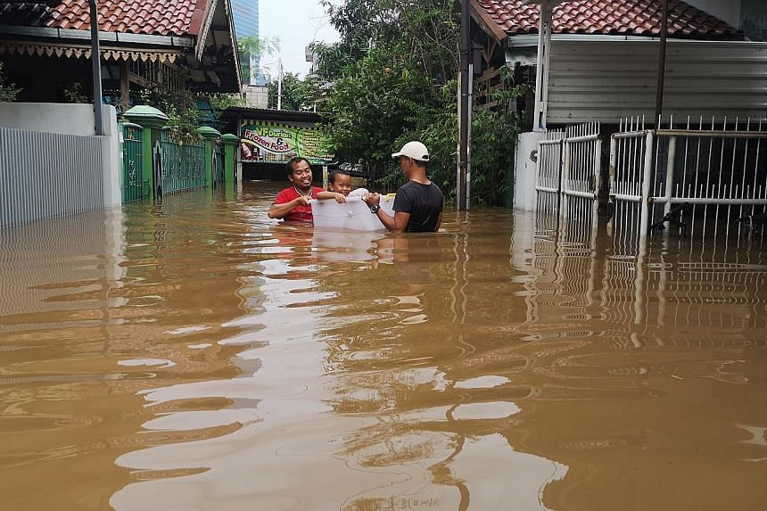 Neighbours outside the writer's house near Krukut River in Jakarta evacuating from their home on New Year's Day.