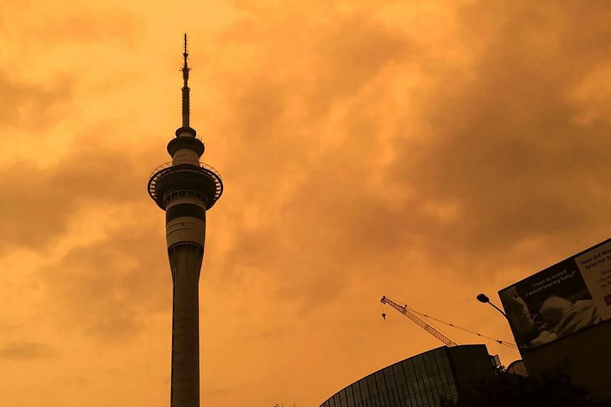 The sky above Auckland's Sky Tower turns orange as smoke from the Australia wildfires arrives in New Zealand on Jan 5, 2020.