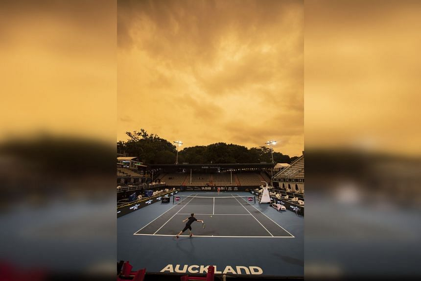 Players practice as the sky turns orange in New Zealand on Jan 5, 2020. The smoke has now moved north and blanketed much of the top half of the North Island.