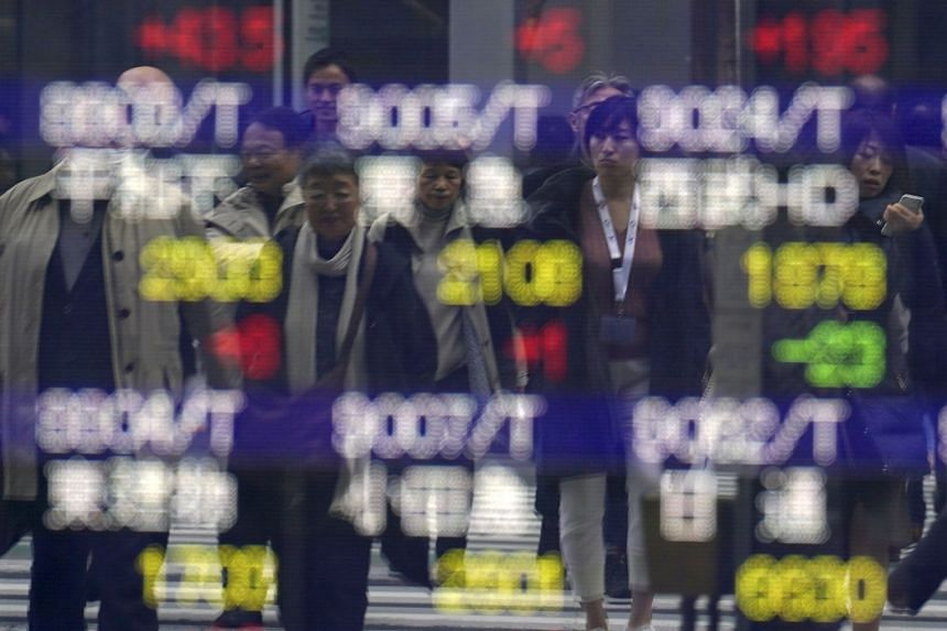Pedestrian are reflected on an electronic stock board showing Japan's Nikkei 225 index at a securities firm in Tokyo, on Dec 13, 2019.
