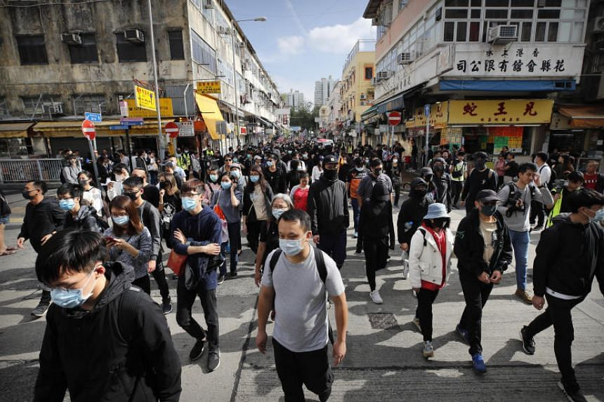 """Protesters march during a demonstration against """"parallel traders"""" who buy goods in Hong Kong to resell in mainland China in Sheung Shui, near the Chinese border in Hong Kong on Jan 5, 2020."""