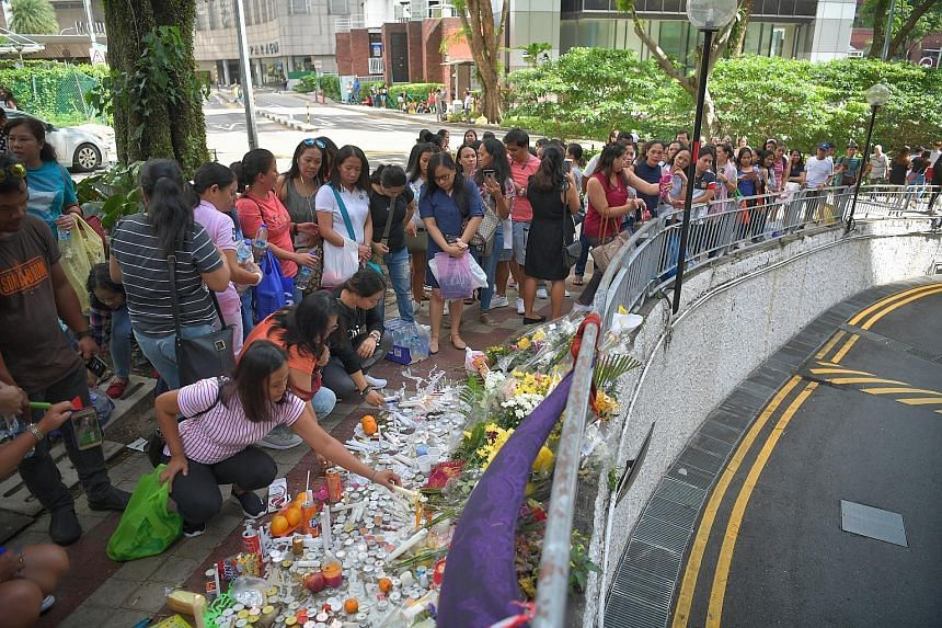 Members of the public, many of them domestic workers, at a makeshift memorial yesterday at the site of the accident which happened on Dec 29. A car making a U-turn near Nutmeg Road had careened into the sidewalk where a group of friends were having a picn