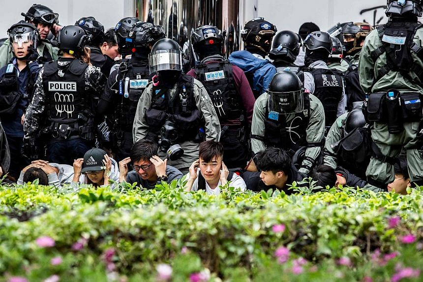 People being detained by police during a clearance operation after a demonstration against parallel trading in Sheung Shui yesterday. The trading practice frequently leaves goods in short supply in border towns.