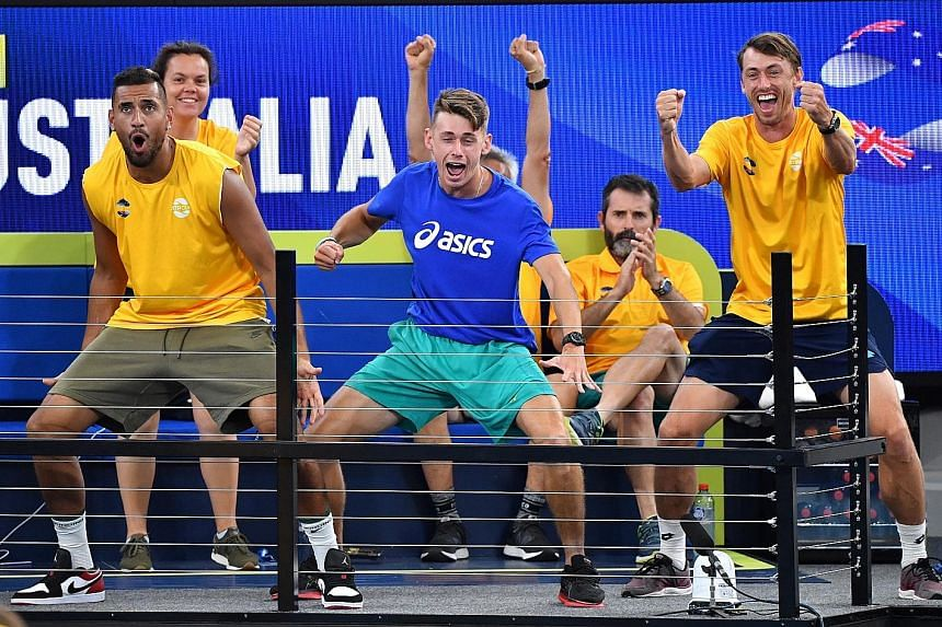 Team Australia players (from left) Nick Kyrgios, Alex de Minaur and John Millman cheering teammates Chris Guccione and John Peers during their doubles match against Felix Auger-Aliassime and Adil Shamasdin of Canada yesterday.