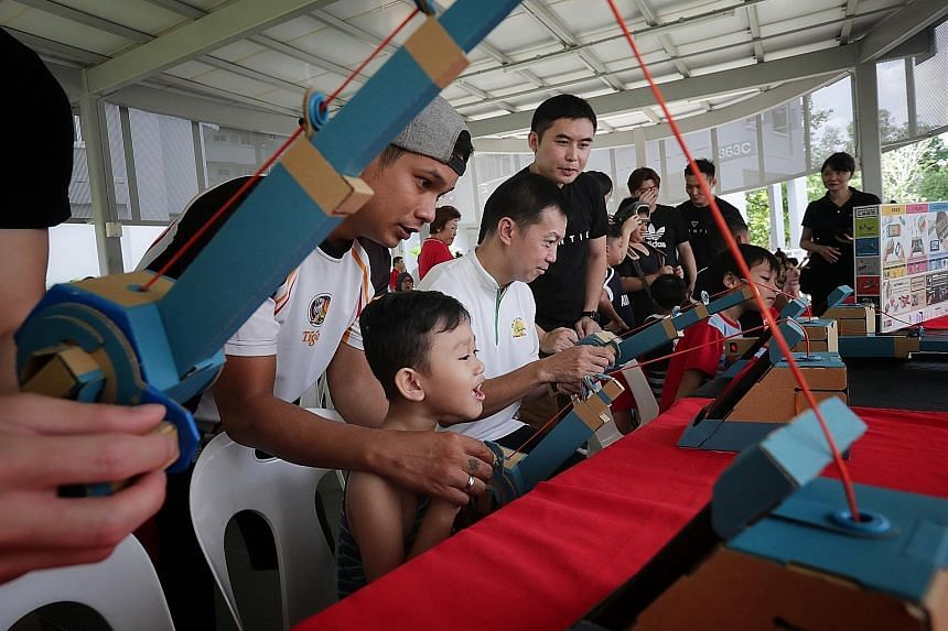 Adviser to Canberra GROs Lim Wee Kiak (seated) trying out a fishing game that uses Nintendo Labo yesterday. The game section was set up by Bountie Technologies as part of a block party organised in conjunction with WeCare @ North West - Service Weeks