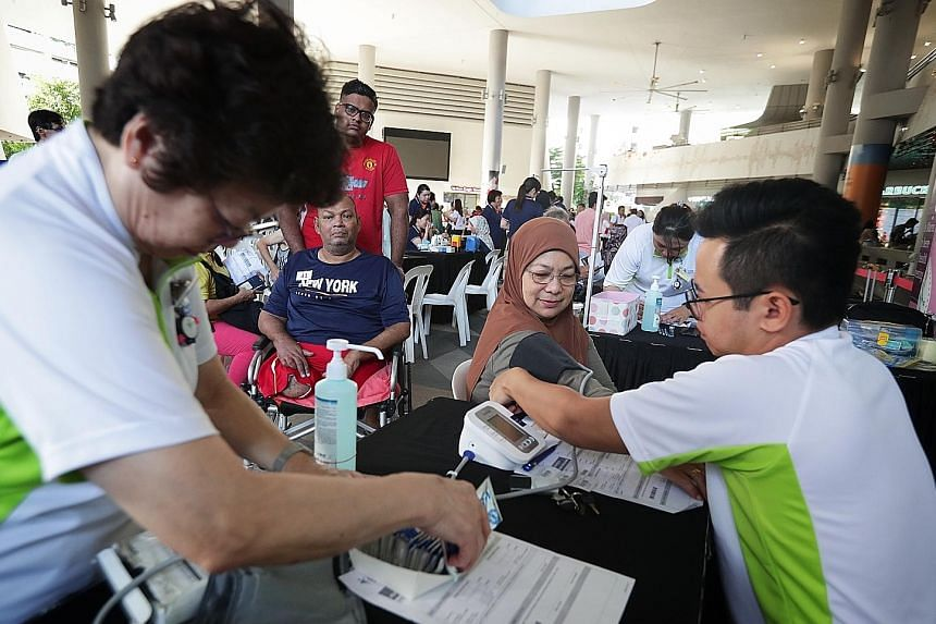 Madam Kamisha Sumadi, 68, having her blood pressure taken yesterday. The event was part of the Health Promotion Board's efforts to encourage health screening and follow-up within the Malay community.