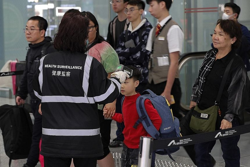 A health surveillance officer checking the temperature of passengers near the immigration counters at the Hong Kong International Airport on Saturday. The latest seven patients in Hong Kong are reported to be in stable condition and quarantined in di
