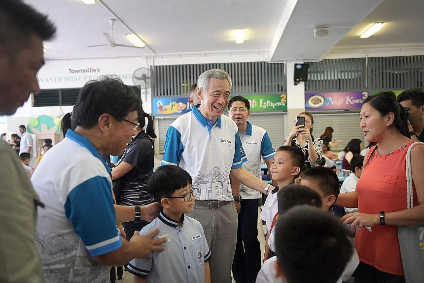 Prime Minister Lee Hsien Loong meeting award recipients and their families at the award ceremony on Saturday at Townsville Primary School. The Teck Ghee CCC Bursary was awarded to 351 students, while another 760 received the MOE Edusave Awards.