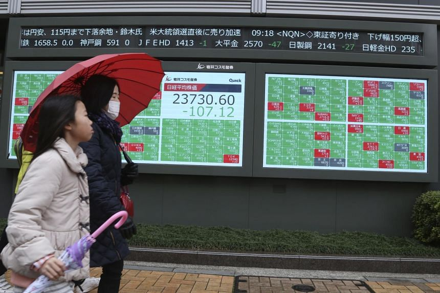 People walking by an electronic stock board of a securities firm in Tokyo, Japan, on Dec. 30, 2019.