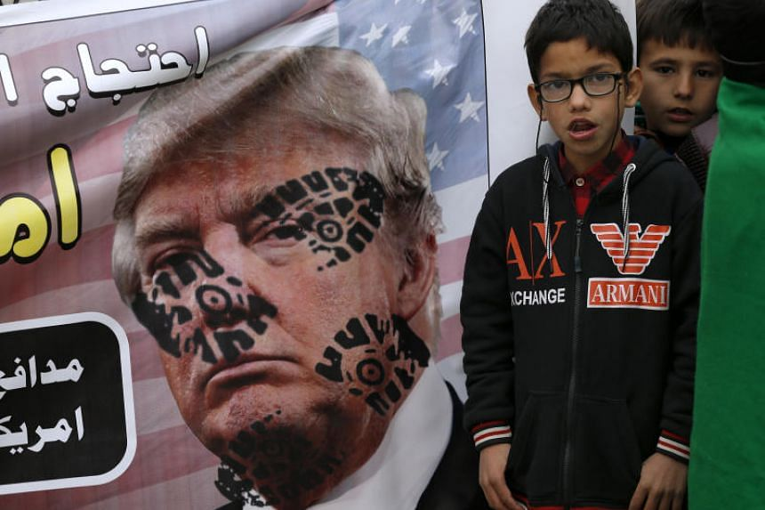 Boys listen to a speech next to a defaced poster of US President Donald Trump during a rally in Islamabad to condemn the killing of Iranian commander Qassem Soleimani, on Jan 5, 2020.