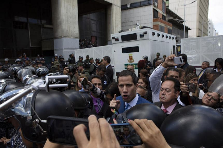 Venezuela's opposition leader Juan Guaido argues with police as he and other lawmakers are stopped a few blocks from the Assembly in Caracas, on Jan 5, 2020.