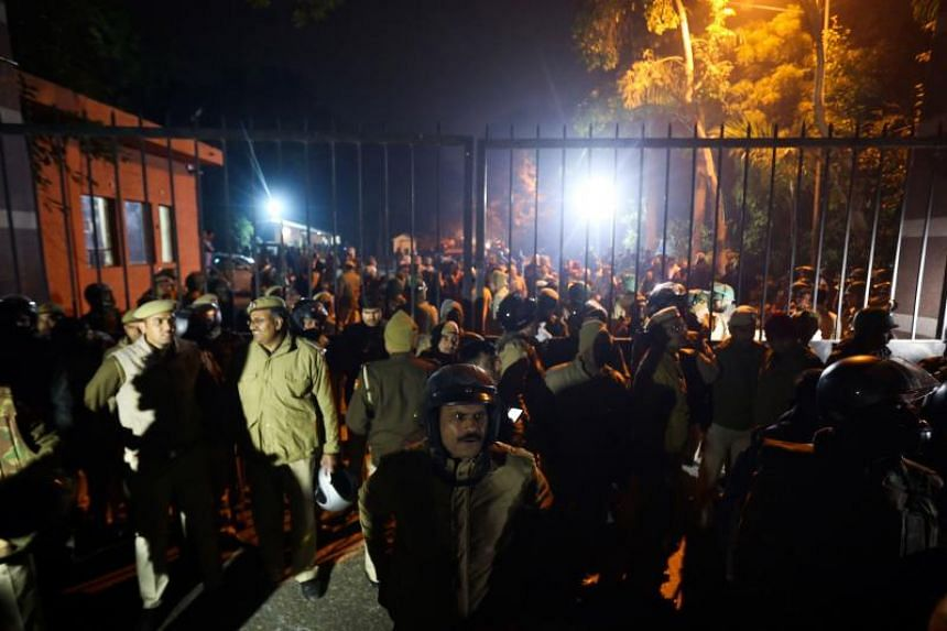 Indian police gather outside a gate of the Jawaharlal Nehru University following alleged clashes between student groups in New Delhi on Jan 5, 2020.