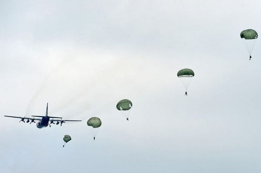 In a photo taken on May 14, 2013, a string of parachutes blooms behind a C-130 Hercules. Defence Minister Ng Eng Hen said the SAF conducts about 6,000 static-line parachute jumps every year.