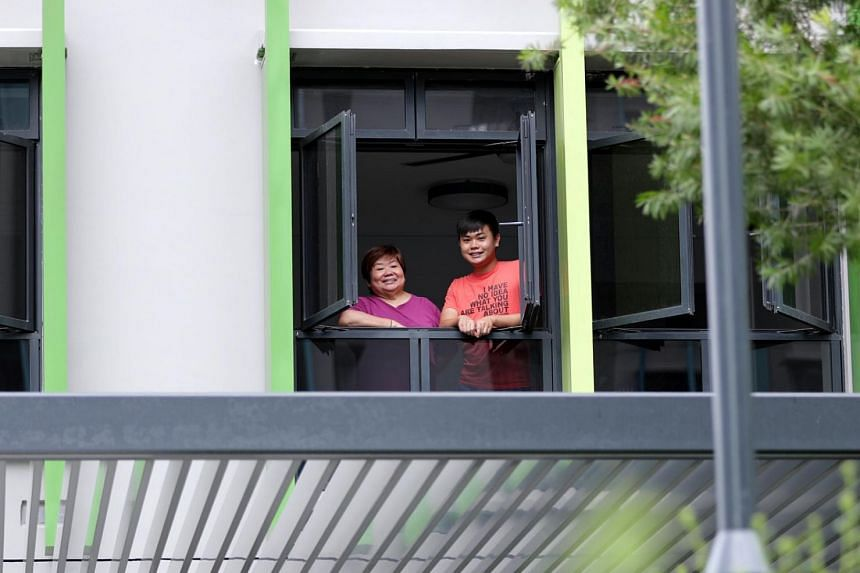 Madam Neo Swan Hoi, 63, and her son Kevin Neo, 27, looking out of their sixth-floor unit in Block 115C in Alkaff Lakeview. They have just completed renovations and plan to move in before the Chinese New Year.