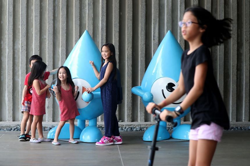 Children playing near the Water Wally mascot at the Marina Barrage.