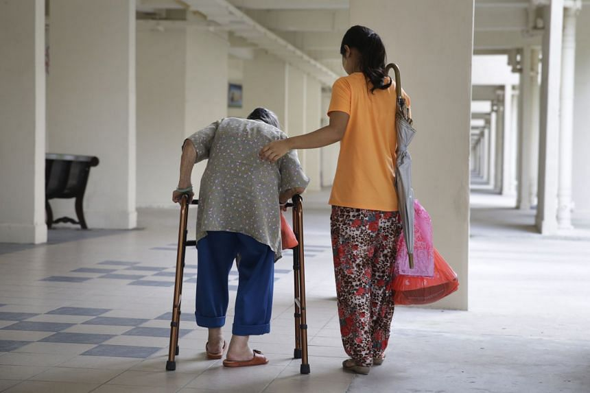 A domestic helper assists an elderly woman to walk with an aid.