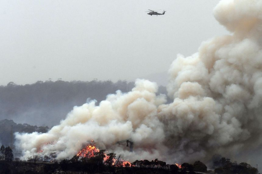 An Australian military helicopter flies above a burning woodchip mill in Eden, New South Wales, on Jan 6, 2020. Singapore is deploying two helicopters to assist Australia's efforts to respond to the bush fire crisis.