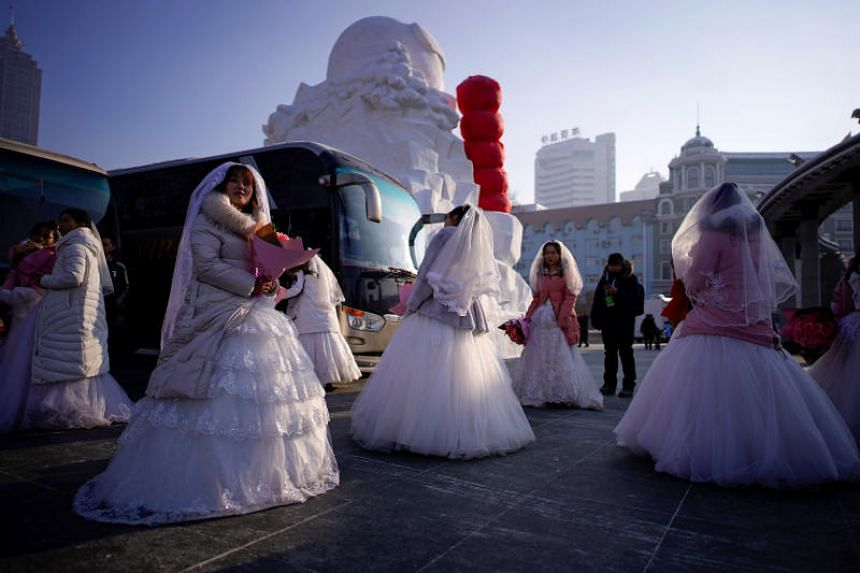 Newlywed couples at a mass wedding ceremony that is a part of the annual ice festival in Harbin, China, on Jan 5, 2020.