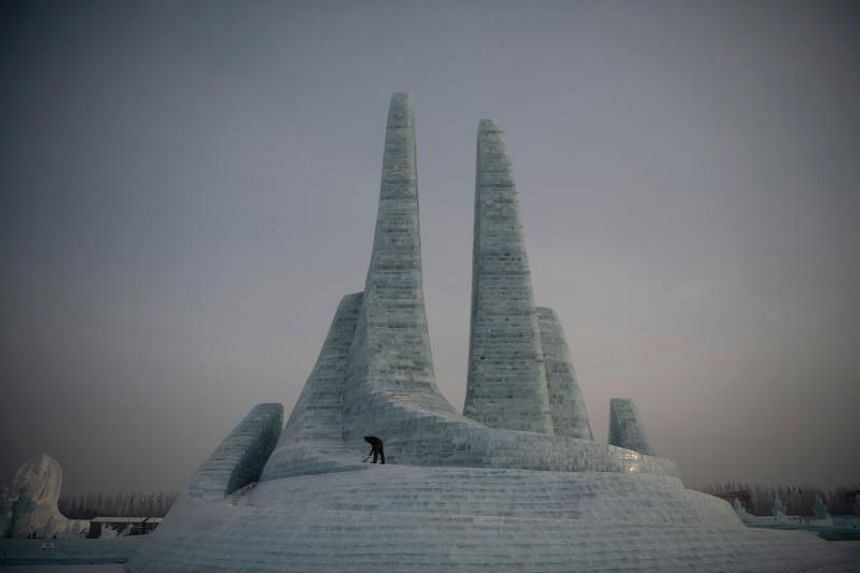 A worker clears some snow at the Harbin International Ice and Snow Festival in Harbin, China, on Jan 6, 2020.