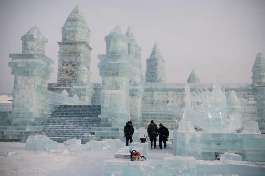 Workers clear snow before people arrive for the Harbin International Ice and Snow Festival in Harbin, China, on Jan 6, 2020.