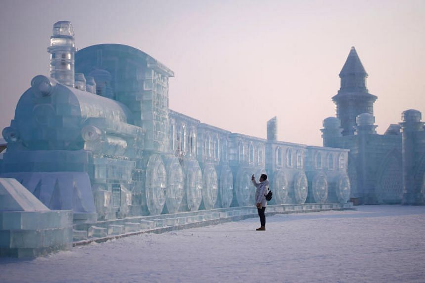 A man visits ice sculptures ahead of the annual Harbin International Ice and Snow Sculpture Festival in Harbin, China, on Jan 4, 2020.
