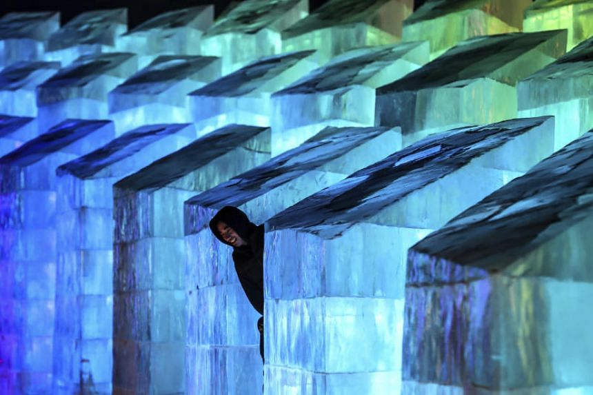 A visitor looks at an ice sculpture on the opening night of the Harbin International Ice and Snow Festival in China on Jan 5, 2020.