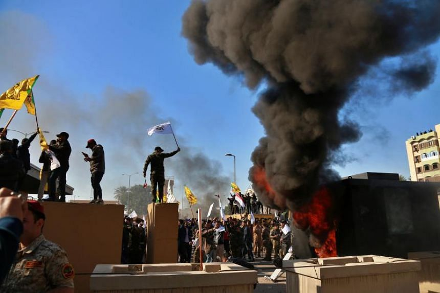 Protesters set fires in front of the US embassy compound, in Baghdad, Iraq, on Dec 31, 2019.