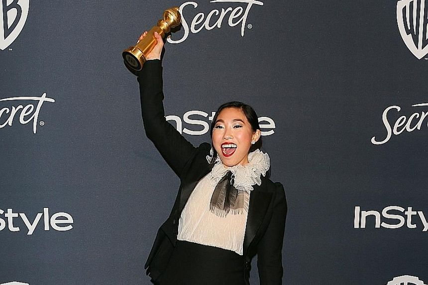 Actress Awkwafina with her award for Best Actress in a Motion Picture - Musical or Comedy.