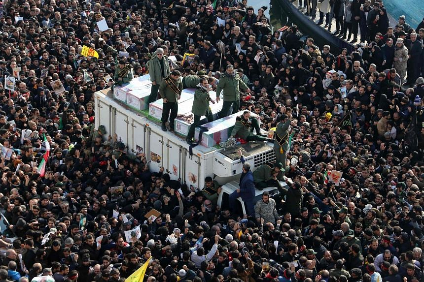 Members of Iran's Revolutionary Guards surrounding the coffins of slain Iranian military commander Qassem Soleimani, Iraqi militia leader Abu Mahdi al-Muhandis and other victims of the US attack as mourners gathered to pay homage in the Iranian capit