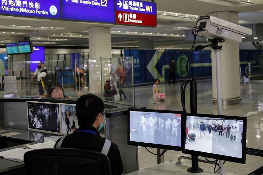 Health surveillance officers use temperature scanners to monitor passengers arriving at the Hong Kong International airport on Jan 4, 2020.