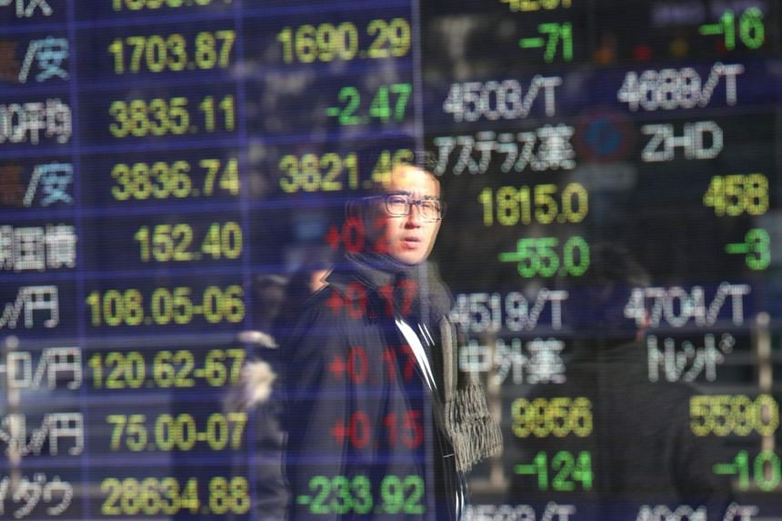 A man is reflected as he looks at a stock indicator showing share prices of Japanese companies, in Tokyo on Jan 6, 2020.