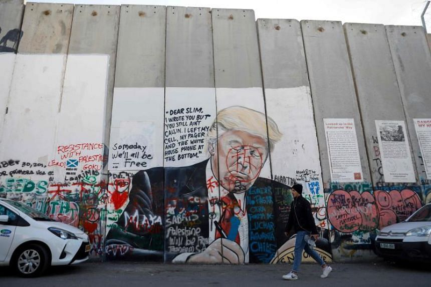 A Palestinian man walk past the vandalised mural painting of US President Donald Trump on Israel's controversial separation barrier in the West Bank city of Bethlehem on Jan 3, 2020.