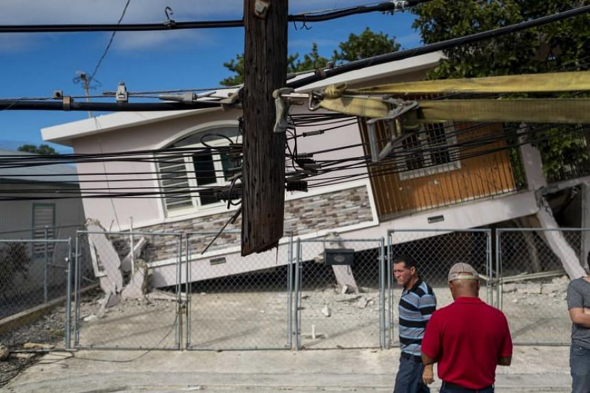 People pass by a house damaged by a 5.8-magnitude earthquake which struck Guanica, Puerto Rico on Jan 6, 2020.