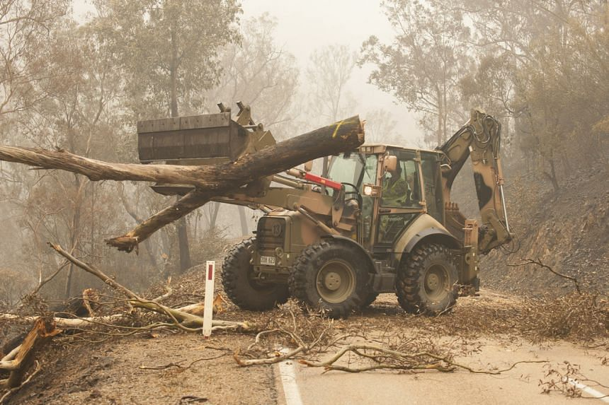 Plant operators Corporal Duncan Keith and sapper Ian Larner of the 22nd Engineer Regiment use a 434 backhoe to assist staff from Forestry Management Victoria to clear fire damaged trees in Australia on Jan 6, 2020.