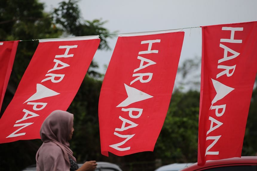 A voter walking past Pakatan Harapan banners. Only 26 per cent felt the country was moving on the right track.