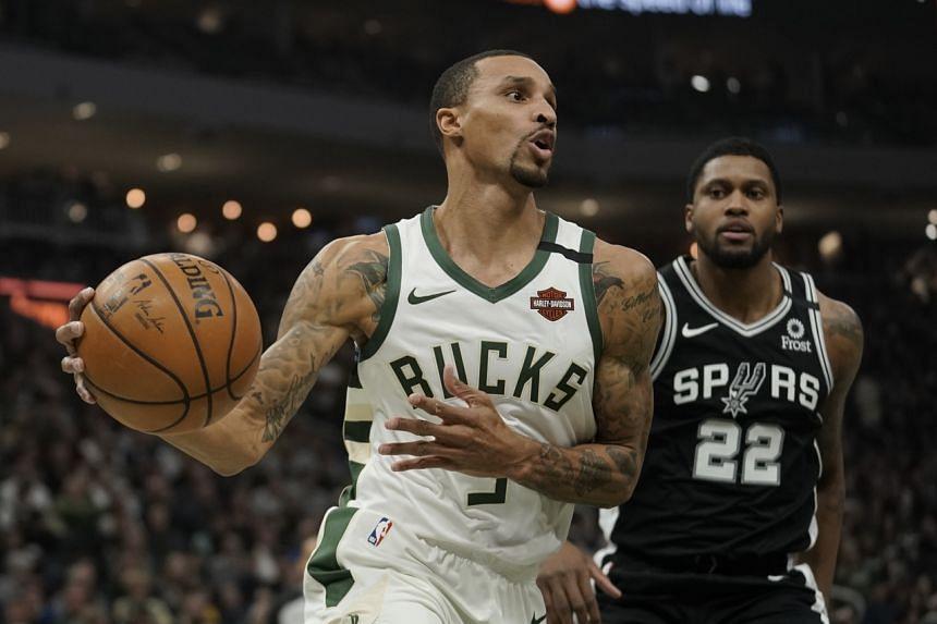 Milwaukee Bucks' George Hill (left) drives past San Antonio Spurs' Rudy Gay on Jan 4, 2020.